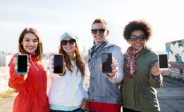 Amis de sourire montrant les écrans vides de smartphone Photos libres de droits