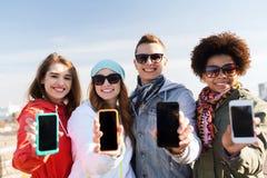 Amis de sourire montrant les écrans vides de smartphone Images stock