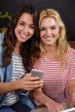 Amis de sourire observant un smartphone ensemble Photographie stock libre de droits