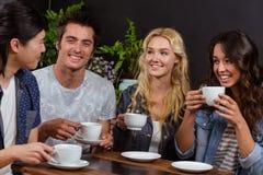 Amis de sourire parlant et appréciant le café Photo libre de droits