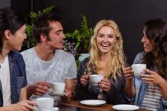 Amis de sourire parlant et appréciant le café Photo stock