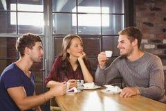 Amis de sourire parlant et appréciant le café et le gâteau Photo stock