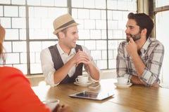 Amis de sourire parlant et ayant le café ensemble Image libre de droits
