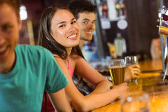 Amis de sourire parlant et buvant de la bière Photos stock