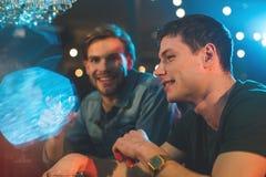 Amis de sourire parlant et buvant des cocktails Photos stock