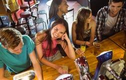 Amis de sourire parlant et buvant la bière et le cocktail Photographie stock libre de droits