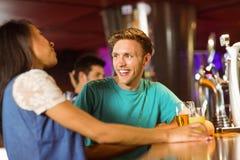 Amis de sourire parlant et buvant la bière et le cocktail Images stock