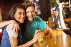 Amis de sourire parlant et buvant la bière et le cocktail Photos stock