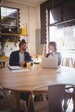 Amis de sourire parlant tout en se reposant avec des technologies au café Photographie stock