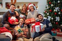 Amis de sourire partageant des cadeaux de Noël Photographie stock libre de droits