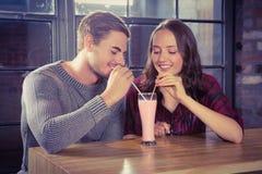 Amis de sourire partageant le smoothie Images libres de droits