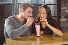 Amis de sourire partageant le smoothie et buvant par des pailles Photographie stock