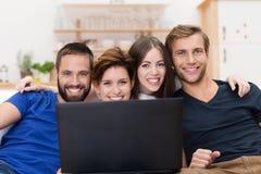 Amis de sourire partageant un ordinateur portable Images libres de droits