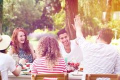 Amis de sourire pendant la réception en plein air Images stock
