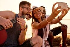 Amis de sourire photographiant avec le musicien fou sur la plage Photographie stock