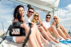 Amis de sourire photographiant sur le yacht Photographie stock libre de droits