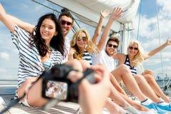 Amis de sourire photographiant sur le yacht Photos stock