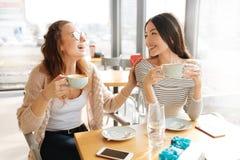 Amis de sourire positifs se reposant dans le café Images stock