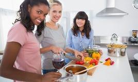 Amis de sourire préparant un repas regardant ensemble l'appareil-photo Image libre de droits