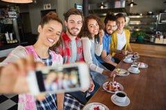 Amis de sourire prenant la photo dans le bar Photographie stock libre de droits
