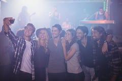 Amis de sourire prenant le selfie dans la boîte de nuit Photos libres de droits