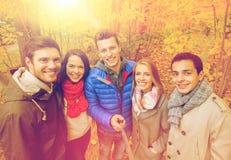 Amis de sourire prenant le selfie en parc d'automne Photographie stock