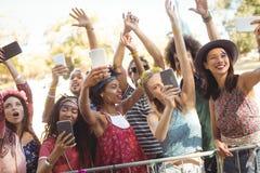 Amis de sourire prenant le selfie par leurs téléphones portables au festival de musique Photographie stock