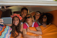 Amis de sourire prenant le selfie tout en se situant dans le camping-car Photographie stock libre de droits