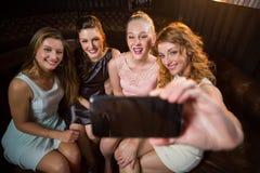 Amis de sourire prenant un selfie de téléphone portable Photos stock