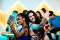 Amis de sourire prenant un selfie de téléphone portable tout en ayant le cocktail Image stock
