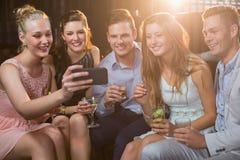 Amis de sourire prenant un selfie de téléphone portable tout en ayant le cocktail Images libres de droits