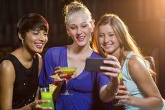 Amis de sourire prenant un selfie de téléphone portable tout en ayant le cocktail Photographie stock