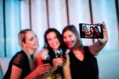 Amis de sourire prenant un selfie de téléphone portable tout en ayant le vin Photo stock