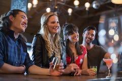 Amis de sourire regardant contre loin dans le bar Images stock