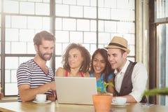 Amis de sourire regardant l'ordinateur portable et avoir le café Image libre de droits