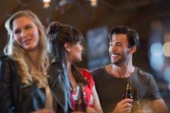 Amis de sourire regardant l'un l'autre tout en tenant le ` de bouteilles à bière Image libre de droits