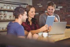 Amis de sourire regardant la tablette Image stock