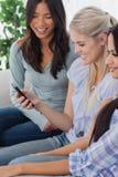 Amis de sourire regardant le smartphone Image libre de droits