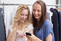 Amis de sourire regardant un smartphone Image libre de droits