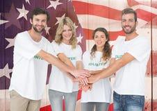 Amis de sourire remontant leurs mains contre le drapeau américain Photo stock