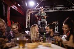 Amis de sourire s'asseyant à la table avec le musicien à l'arrière-plan Photographie stock