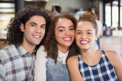 Amis de sourire s'asseyant au restaurant Photographie stock