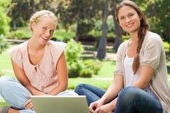 Amis de sourire s'asseyant en parc avec un ordinateur portable Photos stock