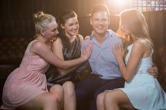 Amis de sourire s'asseyant ensemble dans le sofa Photo libre de droits