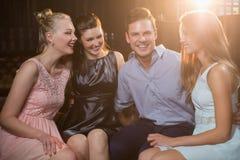 Amis de sourire s'asseyant ensemble dans le sofa Photographie stock libre de droits