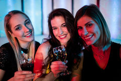 Amis de sourire s'asseyant ensemble et avoir le vin Photo stock