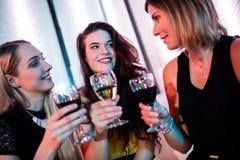 Amis de sourire s'asseyant ensemble et avoir le vin Image libre de droits