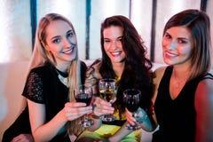 Amis de sourire s'asseyant ensemble et avoir le vin Images stock