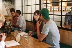Amis de sourire s'asseyant et parlant ensemble à une table de Bistros Photos stock