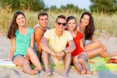 Amis de sourire s'asseyant sur la plage d'été Photos stock